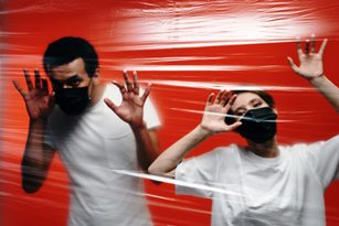 Two people in masks behind plastic barrier