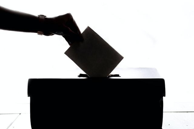 Voter drops a ballot into the ballot box.